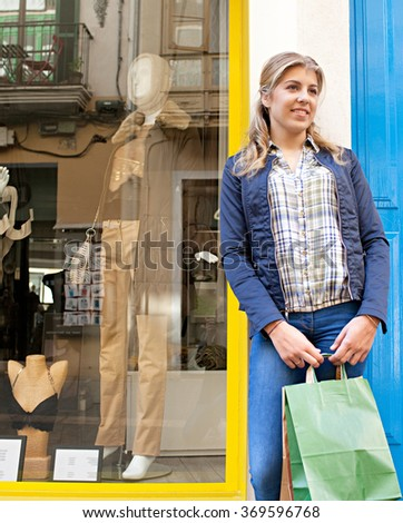 Beautiful teenager tourist girl in high street in a destination city carrying shopping bags, smiling outdoors. Adolescent woman consumer lifestyle in shopping street fashion stores, travel holiday.