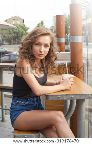 beautiful teenager with a drink on the terrace