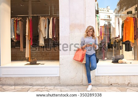 Beautiful teenager young woman in city shopping street by fashion store window, smiling using a smartphone to network online, outdoors. Adolescent consumer using technology, lifestyle exterior. - stock photo
