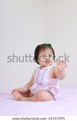 Beautiful ten month old asian baby infant girl in pink and white bodysuit waving