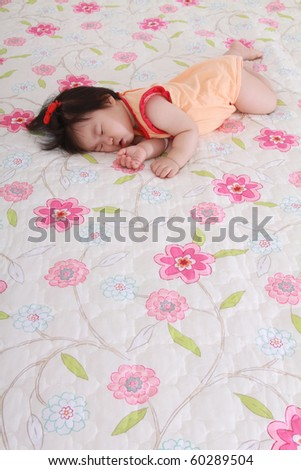 Beautiful ten month old asian baby infant girl sleeping in a deep slumber on a flower print bed dressed in a orange and red body suit