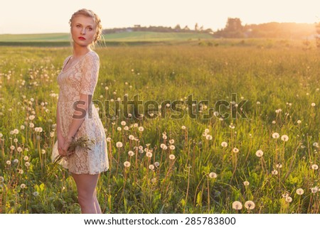 beautiful tender sweet girl in a white lace dress with a scythe on his head standing barefoot in a field of dandelions in the sunset - stock photo