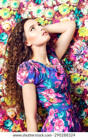 Beautiful tender woman in bright summer dress over floral background. Beauty, fashion. - stock photo