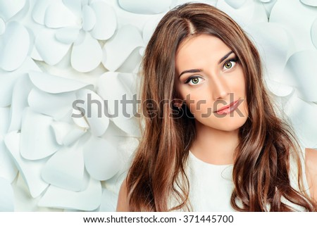 Beautiful tender woman in white dress posing by the background of white paper flowers. Beauty, fashion. Haircare. Cosmetics. - stock photo
