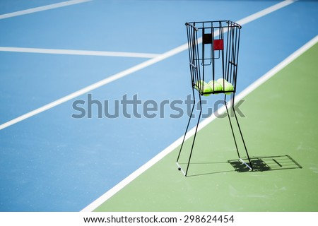 Beautiful tennis court with a ball basket and tennis balls in it - stock photo
