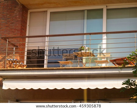 Beautiful terrace or balcony with small table, chairs and flowers - stock photo