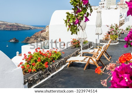 Beautiful terrace with flowers overlooking the sea. White architecture on Santorini island, Greece. - stock photo