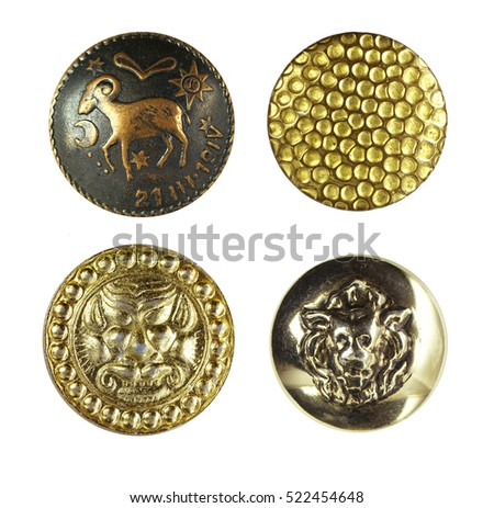 Beautiful textured metal buttons with ornaments and pictures of the gold color close-up macro isolated on white background.