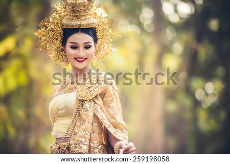 Beautiful Thai lady in Thai traditional drama dress, posing in the forest, greenery in the background, model is Thai Ethnicity. - stock photo