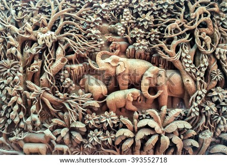 Beautiful Thailand Antique Art Handmade Furniture. Carvings Elephant Family in The Wood on The Wooden Frame used as Antique Design Interior Furniture Hanging on the Wall for Vintage Retro Style Room. - stock photo