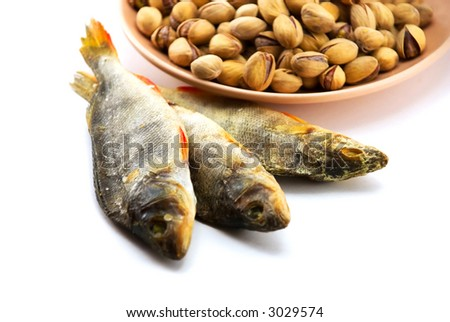 Beautiful the dried perch and pistachioes on a plate on a white background