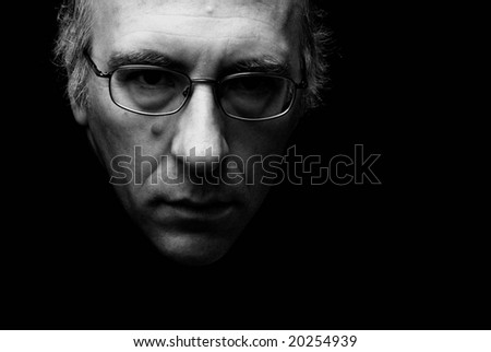 beautiful theatrically lit image of mans face with eyeglasses - stock photo