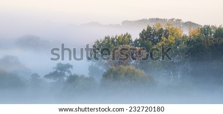 Beautiful thick fog sunrise Autumn Fall landscape over fields with treetops visible through fog - stock photo
