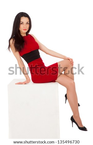 beautiful thin brunette woman in red dress sitting on cube over white background - stock photo