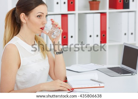 Beautiful thoughtful business woman holding a glass with water looking into the distance. Serious business and partnership, job offer, financial success, certified public accountant concept - stock photo
