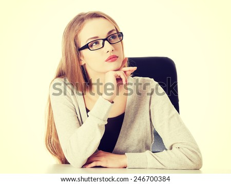 Beautiful thoughtful caucasian woman in eyeglasses sitting. - stock photo