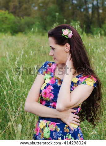 Beautiful  thoughtful woman standing in a forest clearing among the tall grass on a summer evening - stock photo