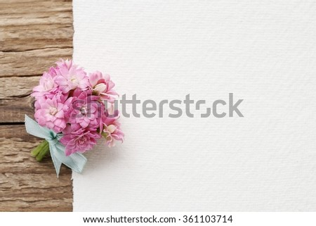Beautiful tiny bouquet of pink kalanchoe blossfeldiana flowers and white sheet of paper, copy space.  - stock photo