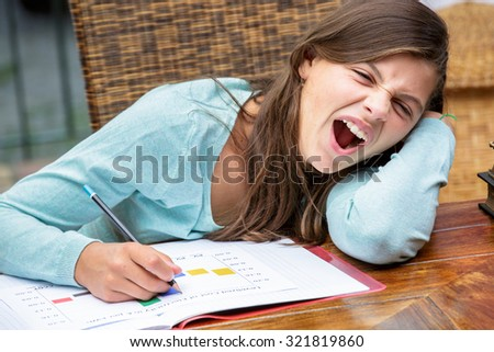 beautiful tired girl student doing her homework while yawning - stock photo