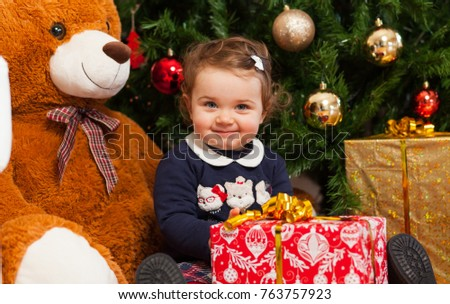 Beautiful toddler baby girl with gifts near christmas tree.