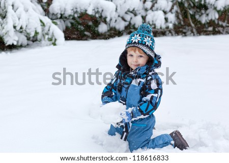 Beautiful toddler boy having fun with snow outdoors on beautiful winter day