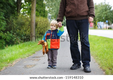 Beautiful toddler boy in colorful clothes and his father walking together