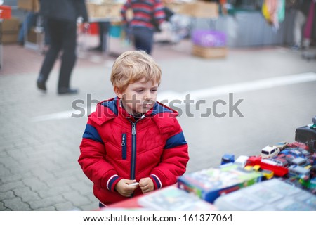 Beautiful toddler boy in red clothes on flea market - stock photo