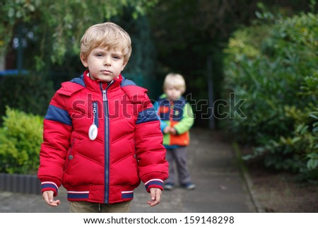 Beautiful toddler boy in red clothes with brother on background