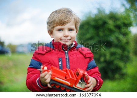 Beautiful toddler boy in red clothes with ship toy in hand - stock photo