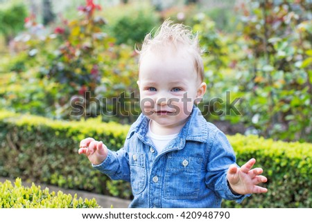beautiful toddler boy looking straight enjoying springtime at the park