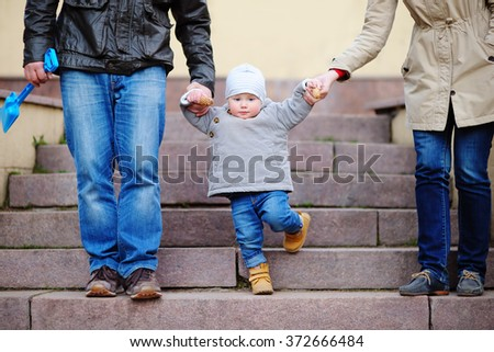 Beautiful toddler boy walking with his parents  - stock photo
