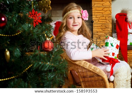 Beautiful toddler european girl with long blond curly hair sitting near fireplace with present box and celebrates Christmas under Xmas tree