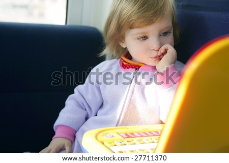 Beautiful toddler little girl thinking playing with yellow laptop toy computer