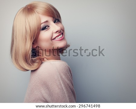 Beautiful tooth smiling woman with short blond hair looking happy. Color toned closeup portrait with empty copy space - stock photo