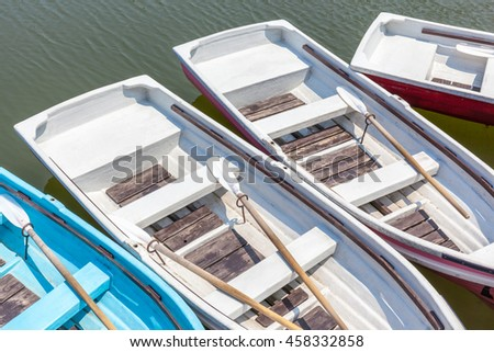 Beautiful top view of wooden rowboats floating around the dock. - stock photo