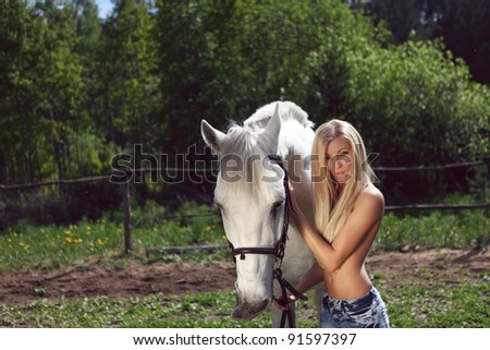 beautiful topless blond woman with a horse in the field