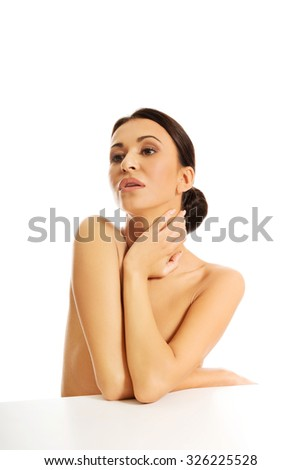 Beautiful topless woman sitting at the desk touching her neck - stock photo