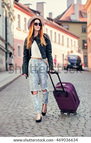Beautiful tourist woman traveling in Europe and walking with suitcase on city street. Concept photo of people travel.