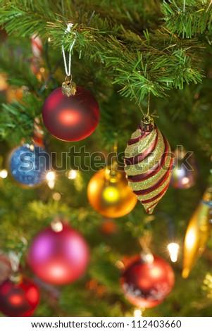 Beautiful traditional christmas decorations on an illuminated xmas tree - stock photo