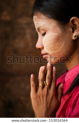 Beautiful traditional Myanmar girl is praying inside temple.
