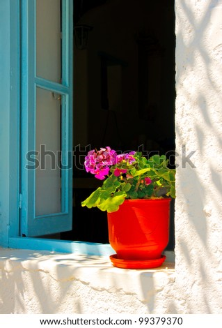 beautiful traditional red colored hand made flower pot out of a window of a house in Chora the capital of Amorgos island in Greece - stock photo