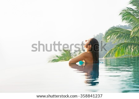 Beautiful, tranquil girl with wet hair swimming in the mountain spa.