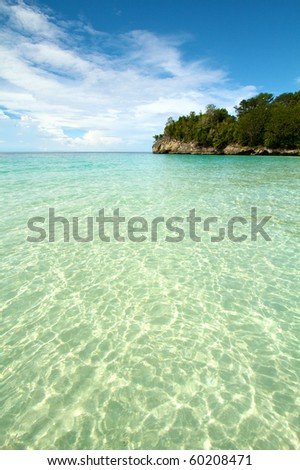 Beautiful tranquil island beach with clear water white sand - stock photo