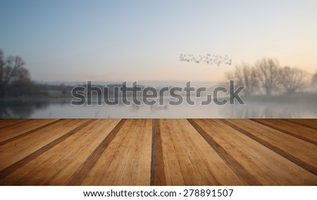 Beautiful tranquil landscape of lake in mist with wooden planks floor