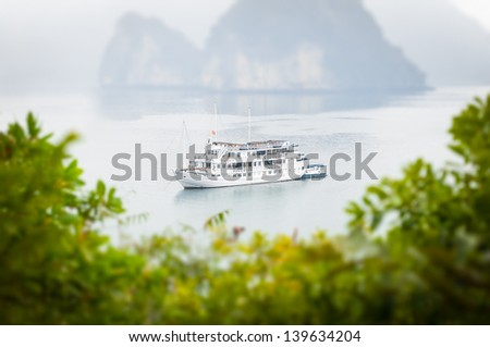 Beautiful tranquil nature of Halong bay. White ship on calm water. Mountains in background, green foliage of trees in foreground. Landscape with fog. Famous tourist destination in Vietnam, Asia. - stock photo