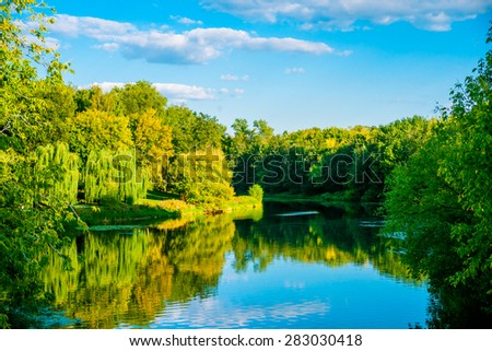 Beautiful tranquil scene  in city park. Green trees surround the river with reflections of blue sky. - stock photo