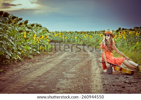 Beautiful traveler on rural road sitting on suitcase over dramatic sunset sky. grain added - stock photo