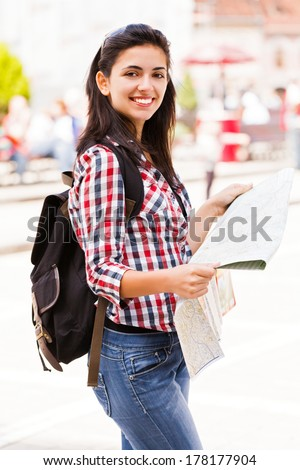 Beautiful traveler with map looking at the camera and smiling. - stock photo