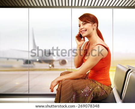 beautiful traveler with mobile phone in airport - stock photo