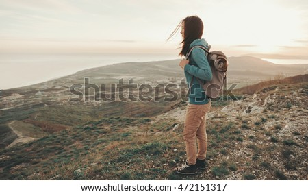 Beautiful traveler young woman with backpack walking in mountains. Toned image